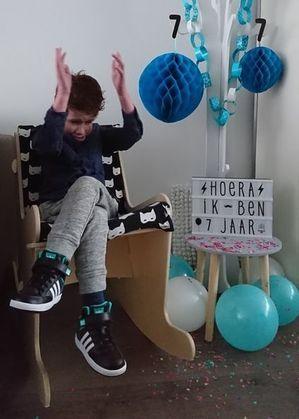 Feest in de houten schommelstoel. Kinderstoel die comfort en ergonomisch is als schoolmeubilair of voor privé.  Zoals je ziet heeft deze jongen plezier in zijn leuke stoel. Stoelen die het verschil maken, Hoera 7 jaar Hoera