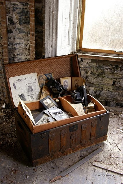 An old wooden chest filled with vintage cameras and  photographs of people that are now dead? Yes, please.