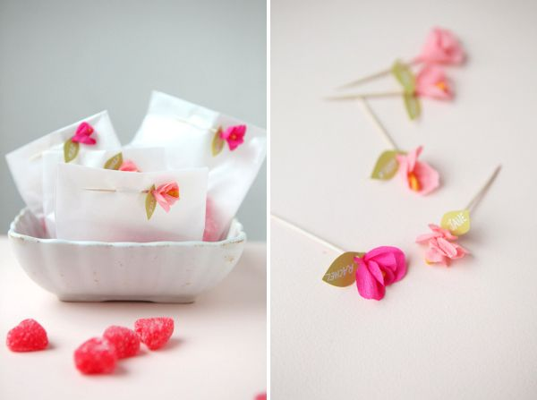 Tiny paper flowers on toothpicks seal these treat bags.