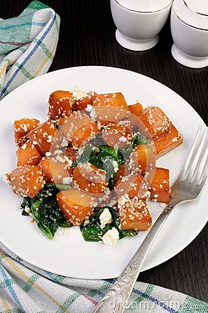 Slices of pumpkin baked with spinach and sesame seeds