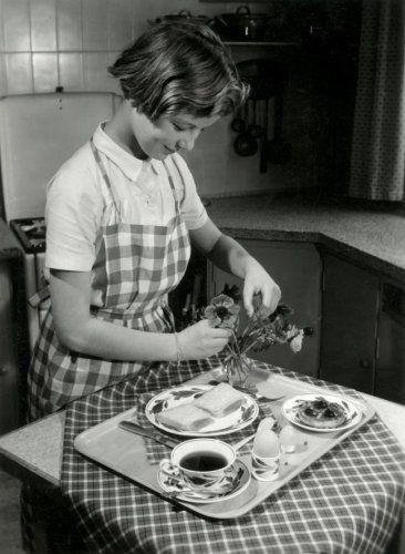 Moederdag. Een meisje in de keuken schikt bloementjes in een vaasje. Het ontbijt voor moeder staat klaar op een dienblad: Brabants bont servies, bordje met twee boterhammen,  bordje met een beschuitje met jam, een kopje thee en een eierdopje met een gekookt eitje. Nederland, mei 1955.