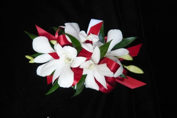 White dendrobium orchids on red ribbons on a velcro wristlet wrist #corsage for #prom by Emil J Nagengast Florist in Albany, NY.