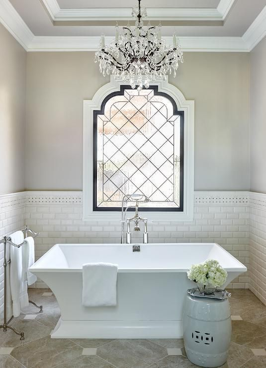 Luxurious French bathroom features a French crystal chandelier hung from a tray ceiling over a freestanding bathtub with a polished nickel tub filler positioned in front of a leaded glass window framed by light gray upper walls and white beveled subway tiled lower walls lined with basket weave border tiles.