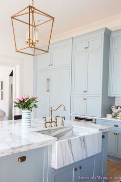 Sweet pastel blue cabinets and Marble farmhouse sink, accessorize with everything golden in colour.