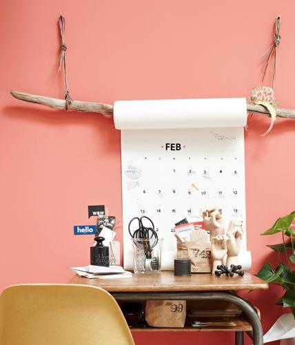 Ein geschälter Ast aus dem Wald hängt an Lederbändern an der Wand und hält die Papierrolle. Die Monate und Tage wurden mit Klebebuchstaben und -zahlen aus dem Bürobedarf aufgeklebt