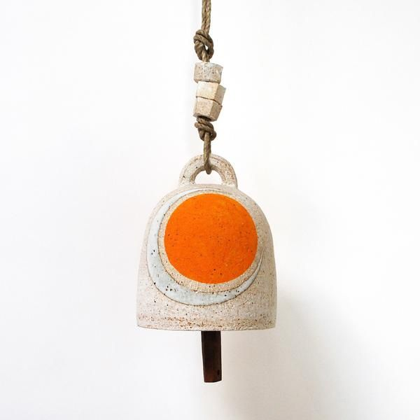 "Small stoneware wheel thrown bell is carved and hand painted Marigold Sun & glazed Crescent Moon Assembled with a reclaimed wood knocker and three small ceramic nut beads on hemp rope  Measures approximately 5.25"" tall x 4.5"" wide Safe to hang outdoors   All work is made to order and ships in 4-6 weeks. Please email sales@mquan.com to enquire about immediate availability"