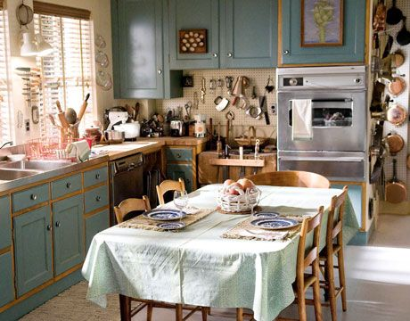"Problem with kitchen: ugly ""oak"" cabinets. Possible solution from Julia child's kitchen: hang artwork on the cabinets, or just reface them with painted cabinet faces and leave the cabinet frames wood."