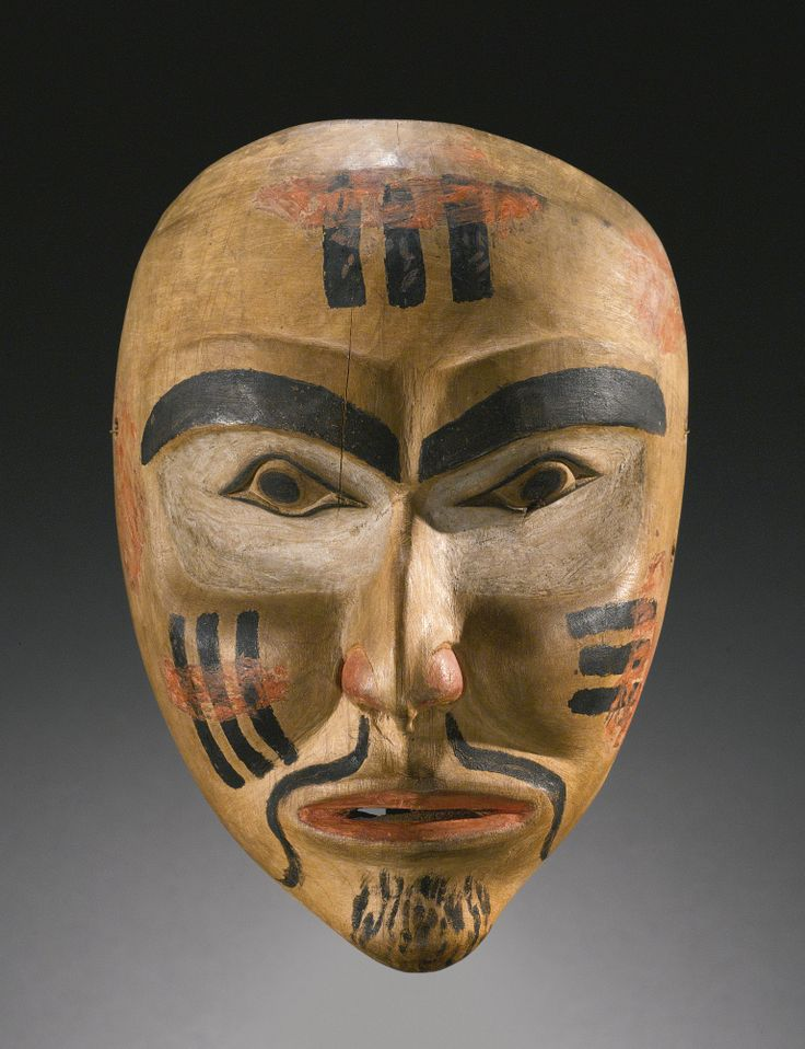 NORTHWEST COAST POLYCHROME WOOD PORTRAIT MASK carved with naturalistic mouth with lips slightly parted, nose with hollowed flaring nostrils, modeled cheekbones, and pointed oval eyerims beneath thick arching brows; the face, forehead and chin painted in red, white and black, with a goatee, and crest designs. height 9 in.