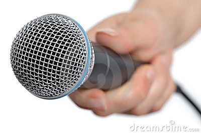 Stock Photo: Womans hand holding a microphone conducting an interview