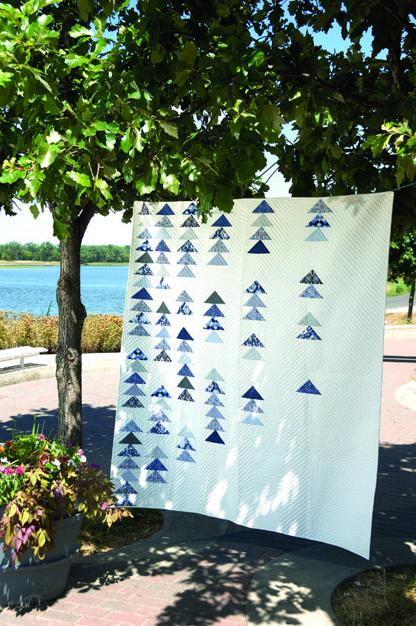 Snow Geese is a modern, white quilt that features blue and gray flying geese units. This quilt goes quickly using fat quarters and only one quilt unit — flying geese. Digital pattern available.