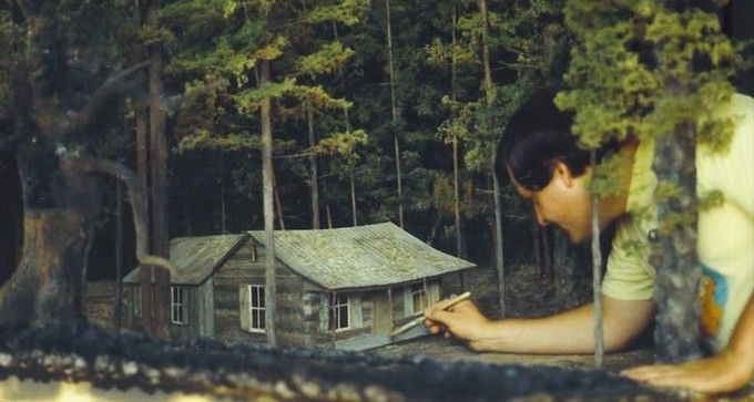 Evil Dead 2: James Belohovek touches up the miniature cabin set where Ash's hacked up girlfriend will rise from the dead.