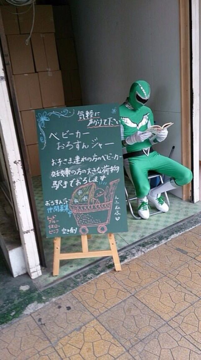 """Real life super hero 27 year-old Tadahiro Kanemasu waits outside Honancho Station to help mothers and the elderly navigate the station stairs, all for free. The chalkboard reads, """"Baby Carriage Carrying Ranger."""""""