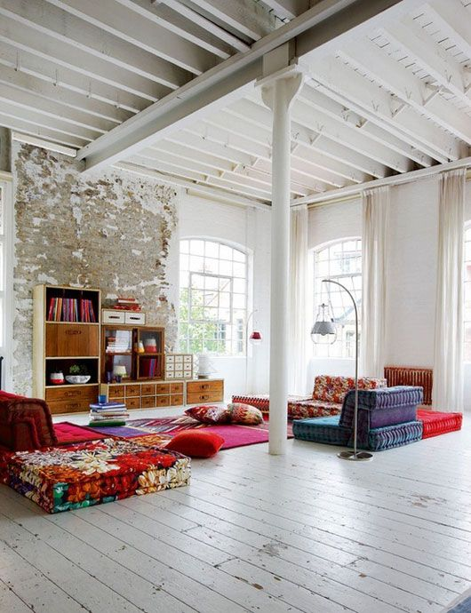 rustic brick, exposed beams, big windows, white floor, colorful furniture.  love