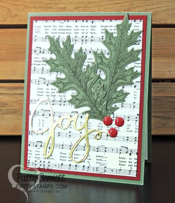 Handmade Christmas card featuring muscial score paper from Stampin' Up! - Home for Christmas paper pack. Joy die cut from Wonderful Wreath framelits and Gold Foil Paper and Vintage Leaves bundle. Card accented with Red Enamel Dots, by Patty Bennett