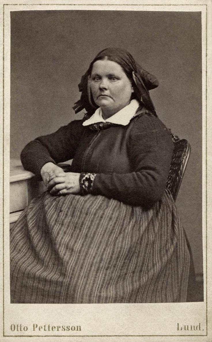 Porträtt av sittande kvinna iklädd huvudduk och randigt förkläde. Knästorp, Bara hd. Gåva från fotograf O. Pettersson i Lund, 1873.