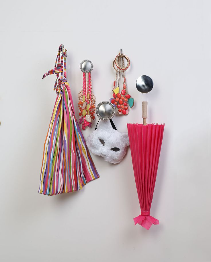 Create a funky storage display using different sizes and styles of metal curtain holdbacks as hooks to hang interesting and colouful items