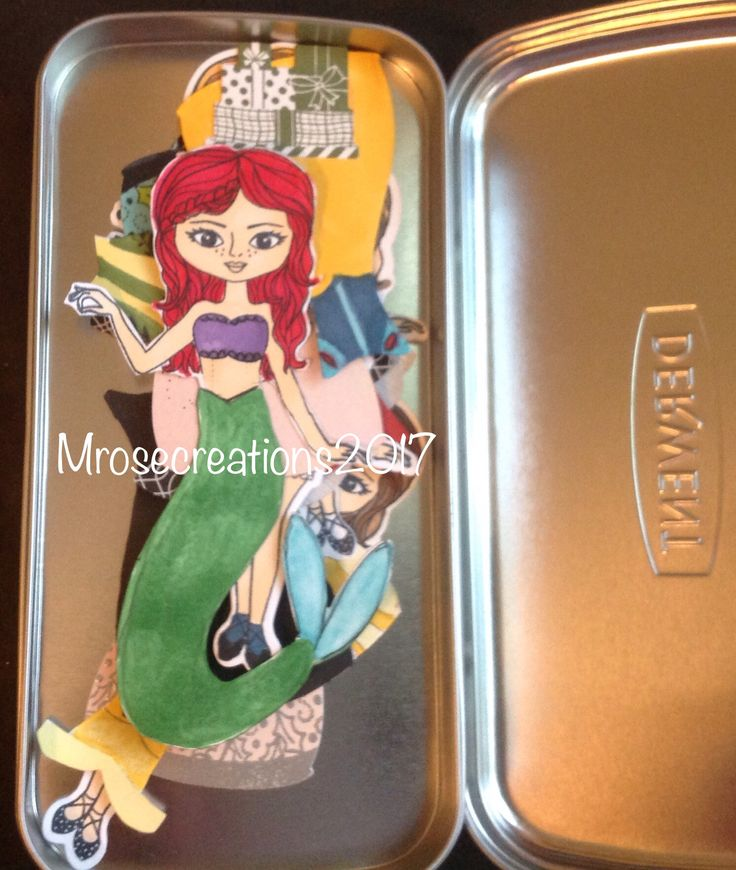 The paper dolls inside the tin.
