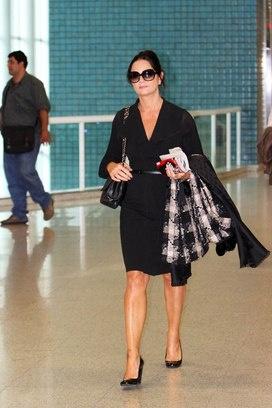Com um vestido envelope preto, sapatos clássicos e um sobretudo, Luiza Brunet novamente arrasa no look