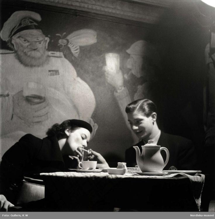 """Ungt par vid ett cafébord, Stockholm, 1948. """"Ungdomar tillbringar sin lediga kväll på konditoriet. Ur radiogrammofonen strömmar eggande dansmusik."""" :) Foto: K W Gullers."""