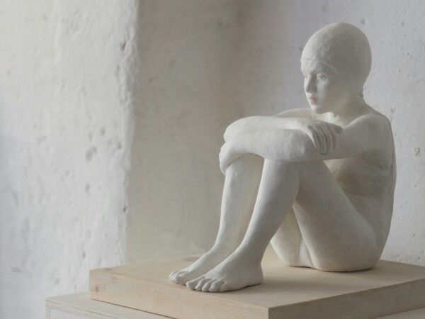 Sculpture of a swimmer sitting by J.isabelle Corniére ( Silence, resin,wood base 2016)