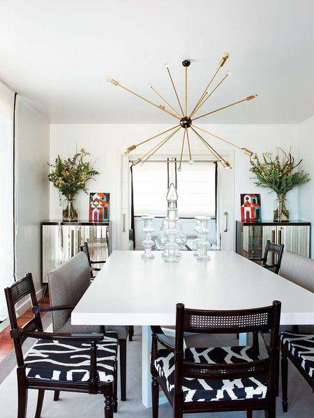 Comedor simétrico con muebles italianos de espejo.