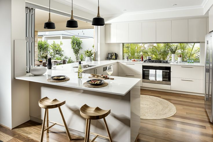 White modern kitchen with glass window splash back and black pendant lights