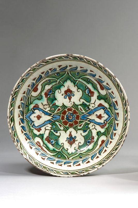 Iznik  Plat rond en céramique siliceuse à glaçure plombifère à décor bleu, rouge et vert au centre d'une fleur formant rosace, cernée de fleurs et palmes sur fond vert.  Début du XVIIe siècle  Diamètre : 28,5 cm