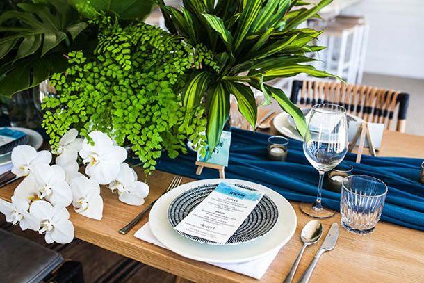 mesa posta de verão com caminho de mesa azul petróleo, prato raso branco, prato de sobremesa azul listrado, taças de cristal e orquídeas e folhagens ao centro.