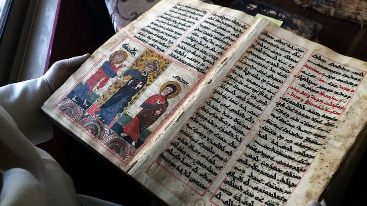 Father Najeeb Michaeel shows off one of the many Christian manuscripts he saved from Iraq's Christian libraries.