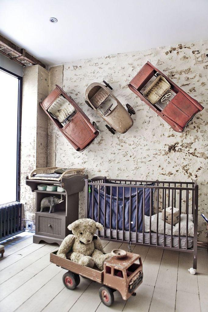 Декоративные элементы из машинок на стене делают эту детскую в стиле лофт абсолютно уникальной. .