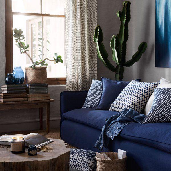 Le bleu marine par petites touches dans le salon avec un canapé bleu marine, des coussins à motifs bleu marine et des vases bleu marine