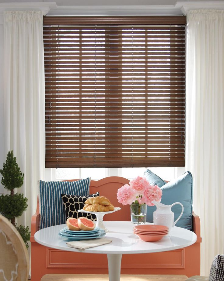 This stylish modern dining room features Parkland® Classics™ custom window treatments. These horizontal blinds are made from basswood and can be painted to match your décor, they look lovely set against the orange and blue colors in this room.
