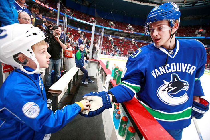 Making friends before the game: Jake Virtanen of the Vancouver Canucks gives Toyota junior trainer Elliott Houghton a puck before a game against the San Jose Sharks on March 29 in Vancouver, British Columbia, Canada. - © Jeff Vinnick/NHLI via Getty Images
