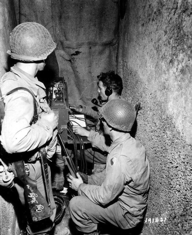 """Signal troops of the 29th Division operate a BD-72 12 line telephone switchboard in St Lo, France. This was the command post of Major Johns, 115th Infantry, 29th Division on the 18th of July, 1944. It was located in the crypt of Mausoleum Strainer in St-Lo cemetery. In the foreground stands a GI with his M1 rifle which he has named """"Cry Baby"""""""