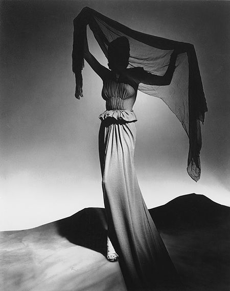 This photograph by George #Platt #Lynes features a dress by Madame Grès, who was known earlier as Alix. The model raises a #chiffon stole in a pose like that of a maenad, a votary of #Dionysos. The classical converges with the #surreal in the setting, an Yves Tanguy-like landscape with an attenuated and faintly distorted figure.