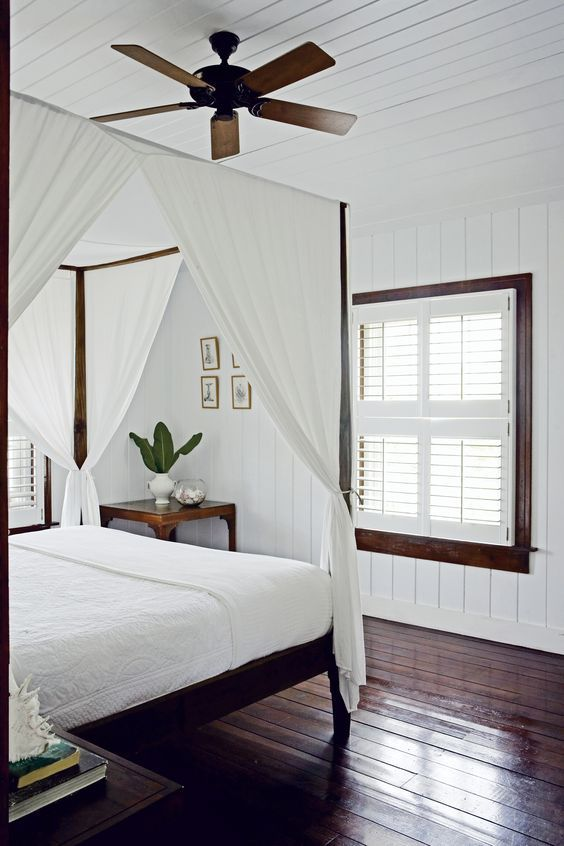 """Longtime Bahamas residents, designer India Hicks and her husband, David Flint Wood built a guesthouse on Harbour Island to accommodate their many visitors. The two-story house was conceived by local architect Henry Melich in an old Caribbean plantation style. Each story has its own wraparound veranda overlooking the beach. """"The beauty of the design is its modular simplicity,"""" says Wood, who created the pencil bed and side table in this bedroom. The aesthetic is clean and uncluttered."""