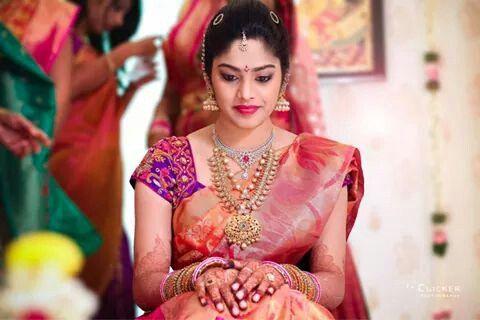 South Indian bride. Pink silk sari. Contrast sari blouse. Jhumki.
