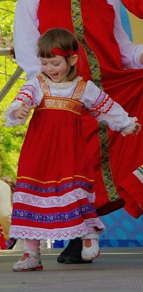 A little Russian girl in a red sarafan (a kind of a sleeveless dress) is singing and dancing at  one of the folk festivals. #kids