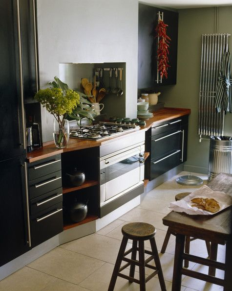 Black Modern Kitchen  A wooden table and stools in the center of a kitchen with black cabinetry.