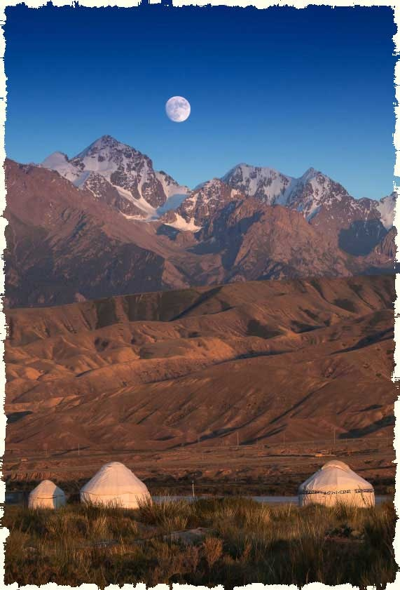 yurts or gers on the mongolian steppe with a full moon behind
