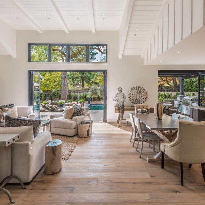 Another view for the farmhouse style living area.  Open kitchen outdoor cooking and pools.  This is an inviting living space for family gathering and hosting friends.   #farmhouse #outdoorliving #outdoorcooking #openkitchen #backyard #farmhouseliving   interiordesign @pamaladeikeldesign photos @paulrollis