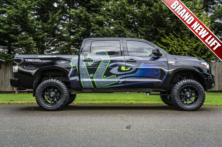 2011 Toyota Tundra Hawks 4x4 with a brand new 6 inch Fabtech Performance Lift Kit with custom navy blue painted suspension components, as well as custom navy blue and green painted 20 inch Fuel Coupler Wheels wrapped in 35 inch Toyo MT Off Road tires. Finishing off the custom look is a the custom made plasma cut Seahawks emblem on the custom mesh grill.