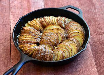 材料(6-8人分):オリーブオイル、じゃがいも6-7個(こちらはレッドポテトを使用)、にんにく5-6かけ(皮をむき、みじんぎり)、イタリアンシーズニング小さじ1、塩こしょう少々、バター1/2カップ(角切り)、パルメザンチーズ1/4カップ(すりおろす)  作り方:①焼き皿にオリーブオイルを塗ります。野菜用スライサーか包丁でじゃがいもをお好みの薄さにスライスし、焼き皿に写真のように並べます。②にんにくのみじん切りとイタリアンシーズニングをじゃがいもの表面にふりかけます。塩こしょうで味を整え、角切りのバターを散らします。③焼き皿をアルミホイルでカバーし、約190℃のオーブンで約1時間いもが柔らかくなるまで焼きます。④焼けたらホイルをとり、パルメザンチーズを散らしてさらに15-20分、少しカリッとするまで焼いたら完成です。
