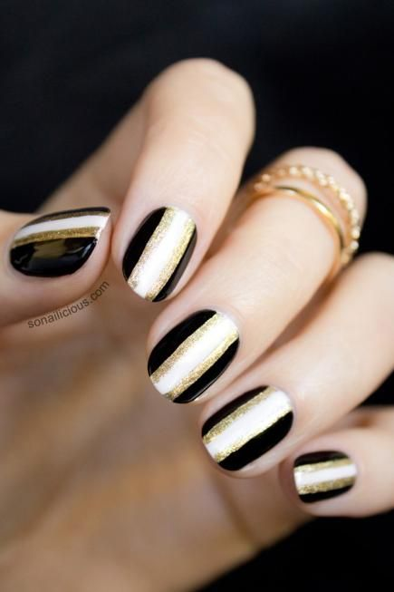 This striped nail design can be formal or casual. For a classic vibe, keep to the simple black-white-and-gold color scheme. #Nails #NailArt
