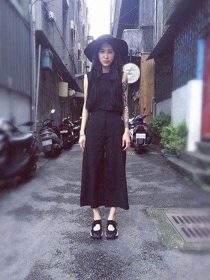 Mona Kuan, wearing a black sunhat, sleeveless top, and wide culottes with Air Rifts.                                                                                                                                                                                 More