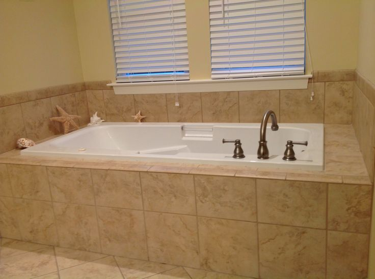Deep jetted tub with tile surround.