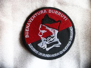 """Parche Buenaventura Durruti  Parche circular del lider anarquista Buenaventura Durruti, con la bandera Rojinegra de fondo y su famosa frase: """"Llevamos un mundo nuevo en nuestros corazones"""". Parche de gran calidad. Termoadhesivo. Medidas: 8 cm de diámetro."""