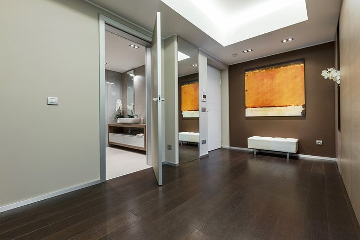 Minimalist Indoor Door Idea To Separate Spacious Hallway From Master Bathroom Elegantly Illuminated By Cove Lighting On False Ceiling