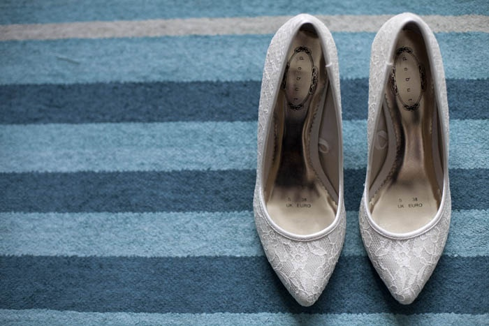 White bridal shoes from above on blue carpet