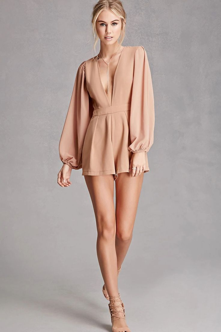 A woven romper by Selfie Leslietrade; featuring a plunging neckline, long sheer sleeves with elasticized cuffs, pleated shorts, on seam pockets, and a hidden back zipper